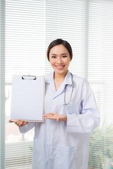 아시아 젊은 여성 의사는 병원에 서 있는 동안 빈 클립보드를 가리키며 화를 냈습니다.