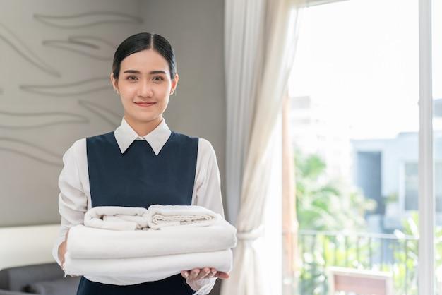 Азиатская молодая горничная отеля в униформе держит чистые свежие белые полотенца в спальне отеля
