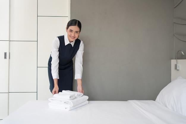 Азиатская молодая горничная отеля в униформе с чистыми свежими белыми полотенцами и заправляет постель в спальне отеля