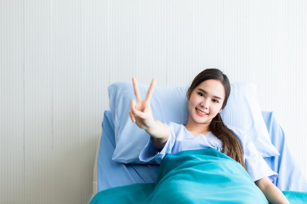 Asian young female patient smiley face lifts two fingers up fighting with illness on bed in the room hospital