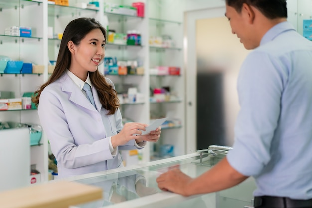Asian young female pharmacist with a lovely friendly smile and receive medicine prescription from man patient.