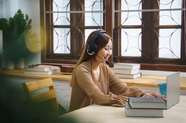 헤드셋을 사용하는 아시아의 젊은 여성 학생은 노트북 화면에서 듣고 온라인 과정을 학습합니다.