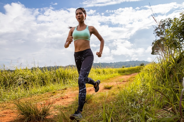 Asian young fitness woman exercise running at forest trail.