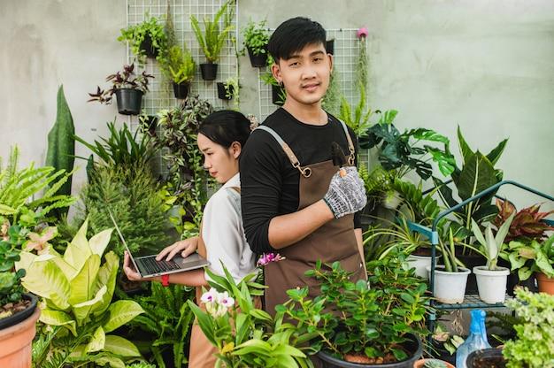 앞치마를 입은 아시아 젊은 정원사 부부는 정원 장비와 노트북 컴퓨터를 사용하여 온실에서 집 식물을 연구하고 돌봅니다.