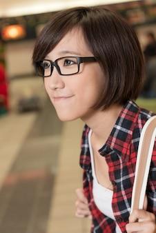 近代都市の通りでアジアの若い女の子。