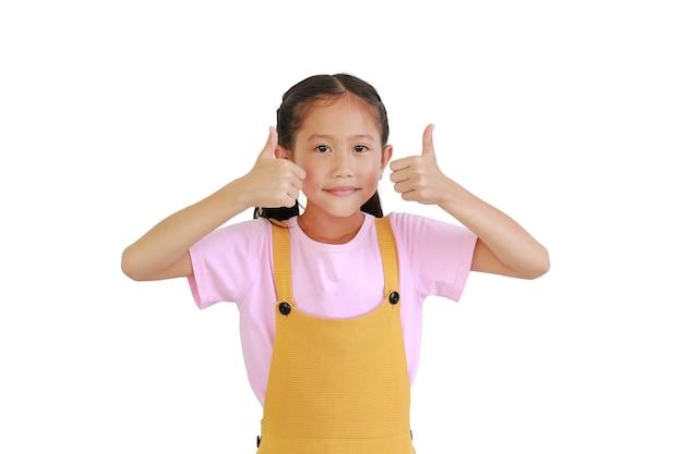 아시아 어린 소녀 아이는 흰색 배경 위에 격리된 두 개의 엄지손가락을 보여줍니다.