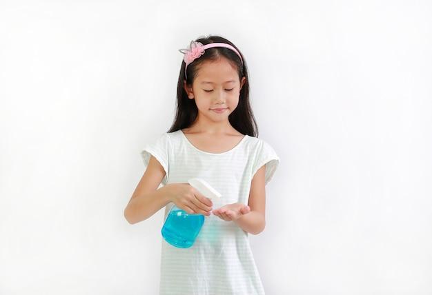 병 스프레이 알코올 액체를 사용하여 흰색 배경에 대한 코로나바이러스 전염병 발병에 대비한 아시아 어린 소녀