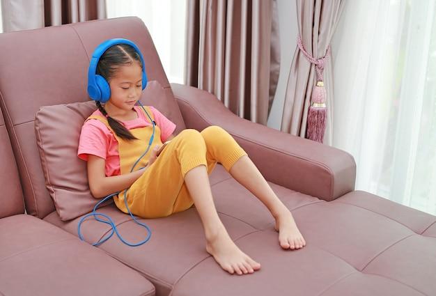 ヘッドフォンを着用し、自宅のリビングルームのソファでスマートフォンを使用してアジアの若い女の子の子供