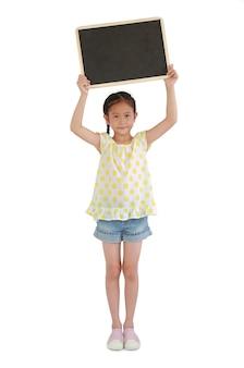 흰색 배경에 고립 된 머리 위에 빈 칠판을 들고 아시아 어린 소녀. 전체 길이