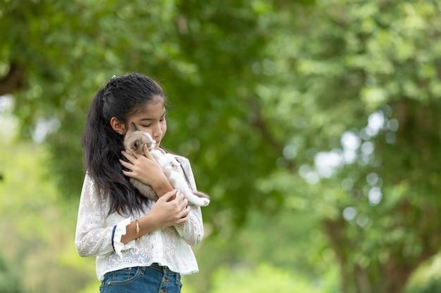 Азиатская молодая девушка держит котят в парке