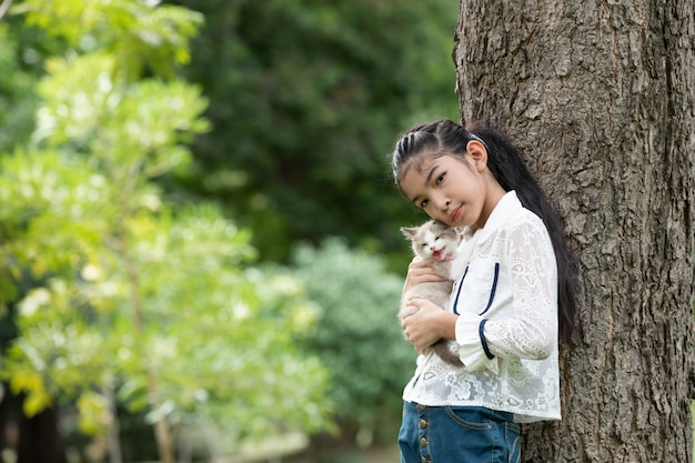 Asian young girl holding kittens in the park