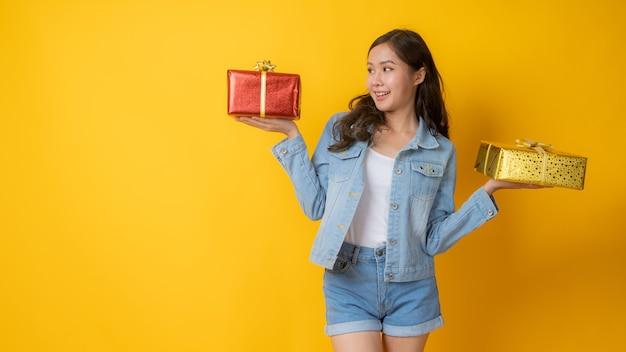 Азиатская молодая девушка в джинсах держит два подарка и думает выбрать