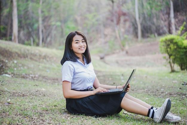 Азиатская маленькая девочка в школьной форме использует компьтер-книжку для образования и связи на сельской местности таиланда.