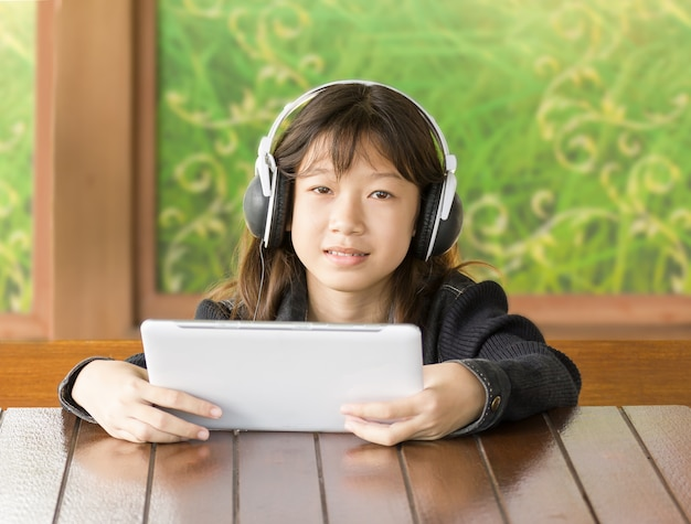 Asian young girl is listening to music through headphones