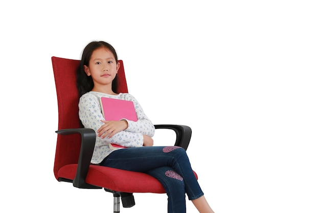 白い背景で隔離の赤い布の椅子に座っている本を抱き締めるアジアの若い女の子の子供。クリッピングパスのあるスタジオの画像