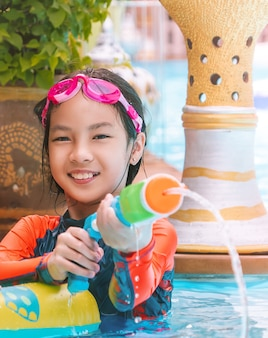 Asian young girl kid is playing with water gun in a tropical resort in thailand.