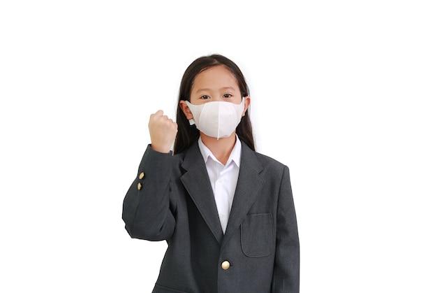 포멀웨어 셔츠, 학생복, 보호용 얼굴 마스크를 쓴 아시아 어린 소녀는 코로나바이러스와 독감 발병 동안 흰색 배경에 격리된 싸움 제스처를 보여줍니다.