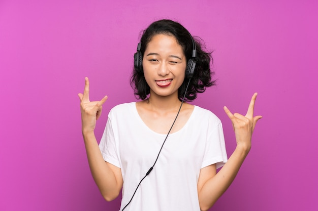Asian young girl listening music with a mobile over isolated purple wall