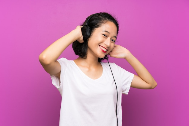 Asian young girl listening music with a mobile over purple wall