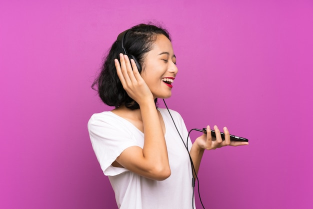 Asian young girl listening music with a mobile and singing over isolated purple wall
