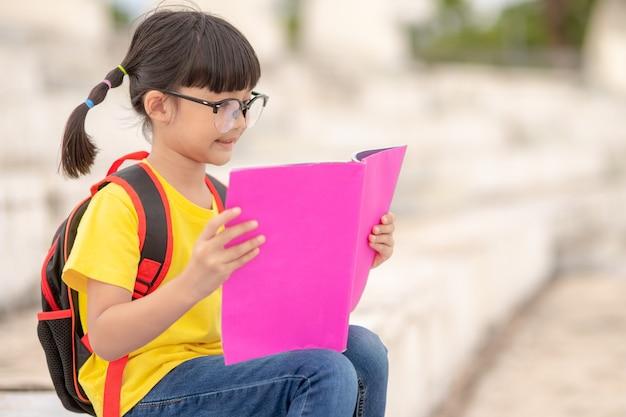 アジアの若い女の子は本を読む、学習スキルの概念。