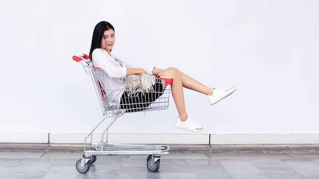 Asian young girl sitting in shopping cart for marketing concept