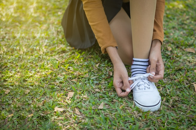 Asian young girl tying her shoelaces after walking in the park