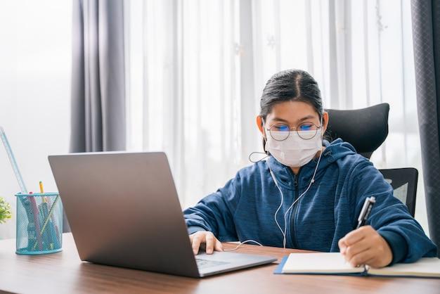 アジアの若い女の子は眼鏡をかけたマスクを身に着けていますヘッドフォン女の子は自宅でビデオ会議ラップトップコンピューターオンラインインターネット学習遠隔教育を探している本に幸せな書き込みメモを勉強