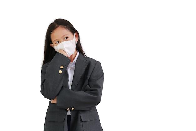 아시아 어린 소녀는 정장 셔츠, 학생복, 보호용 안면 마스크를 착용하고 팔짱을 끼고 흰색 배경 위에 고립된 위를 올려다보며 생각하는 포즈를 취합니다.