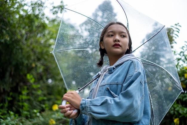 アジアの若い女の子は雨の中でジーンズのコートを着ています。