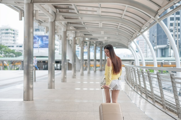 Asian young girl wearing casual dress with dragging luggage on corridor bridge in the city