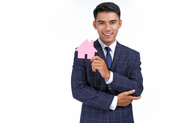 Азиатский молодой красивый и веселый деловой человек держит значок
