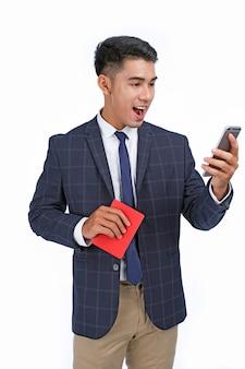 アジアの若いハンサムな陽気なビジネスマンはパスポートと航空券を保持します