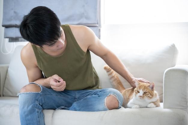 アジアの若いハンサムな男と猫