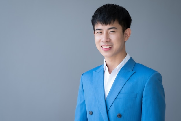 Asian young handsome man smiling in suit