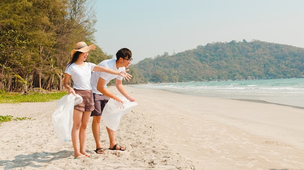 해변에서 플라스틱 폐기물을 수집하는 아시아 젊은 행복한 가족 운동가. 아시아 자원 봉사자들은 자연을 깨끗하게 유지하고 쓰레기를 줍도록 도와줍니다. 환경 보전 오염 문제에 대한 개념.