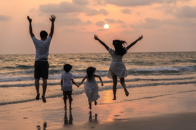 Asian young happy family enjoy vacation on beach in evening. dad, mom and kid relax running together near sea while silhouette sunset. lifestyle travel holiday vacation summer concept. Free Photo
