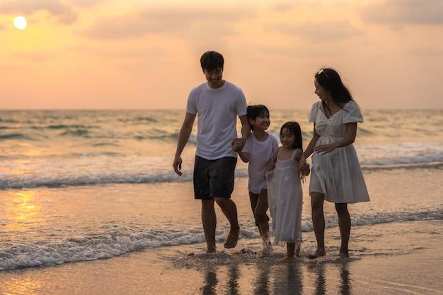 Азиатская молодая счастливая семья наслаждается каникулами на пляже в вечере. папа, мама и ребенок отдыхают вместе гуляя возле моря во время заката во время путешествия. образ жизни путешествия праздник каникулы лето концепция.