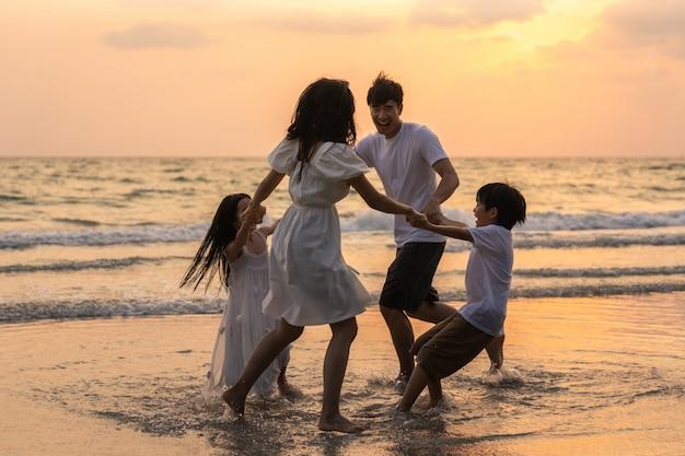 Азиатская молодая счастливая семья наслаждается каникулами на пляже в вечере. папа, мама и ребенок расслабиться, играя вместе возле моря, когда силуэт закат. образ жизни путешествия праздник каникулы лето концепция.