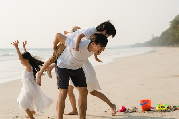 아시아 젊은 행복 한 가족은 저녁에 해변에서 휴가를 즐길 수 있습니다. 여행 휴가 동안 일몰시 아빠, 엄마와 아이가 바다 근처에서 함께 놀고 휴식을 취하십시오. 라이프 스타일 여행 휴가 휴가 여름 개념.
