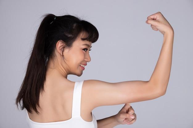 アジアの若い健康的なフィットネス女性のエクササイズは、腕に彼女の筋肉を示し、浮気は小さな平らな筋肉を押し上げます