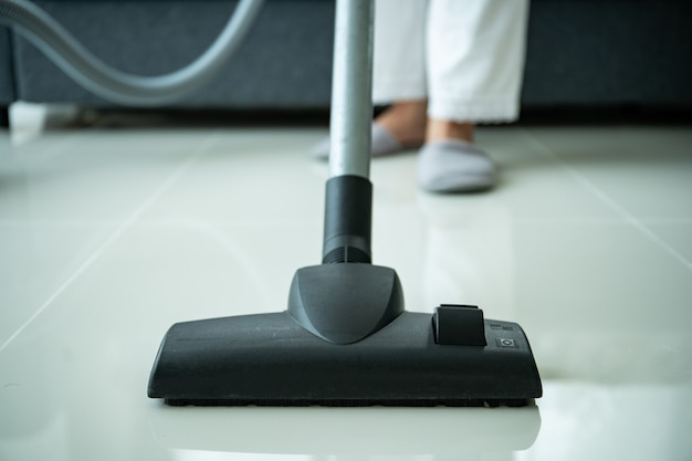 Азиатская молодая домработница, использующая пылесос для очистки грязного пола в гостиной, крупным планом с copyspace. домохозяйка пылесосит пол и диван в гостиной.