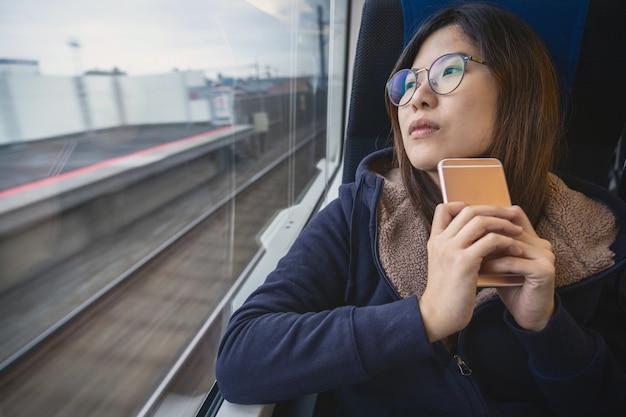 Азиатская молодая пассажирка, сидящая в подавленном настроении у окна в поезде, который путешествует