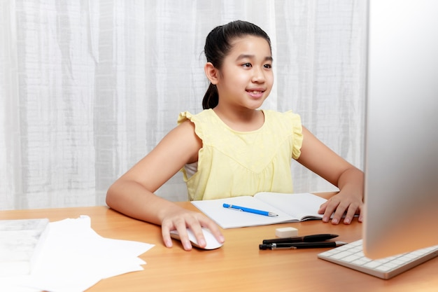 Asian young little girl using pencil to do homework by herself