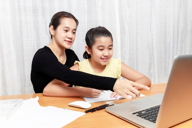 Asian young little girl using pencil to do homework with her mother