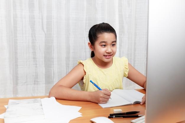 Азиатская молодая маленькая девочка с помощью карандаша делать домашнее задание сама