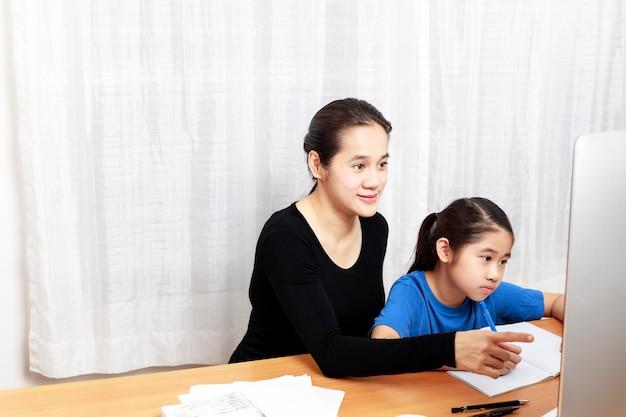 彼女の母親と宿題をするために鉛筆を使用してアジアの若い女の子