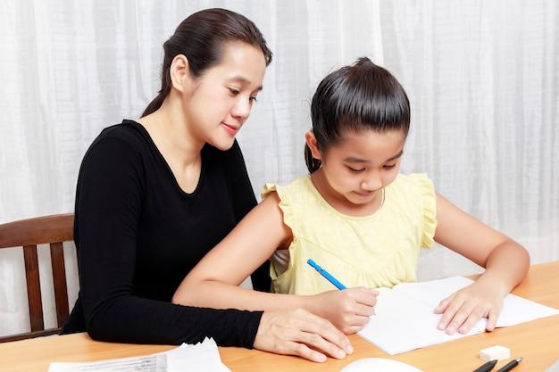 Азиатская молодая маленькая девочка с помощью карандаша делает домашнее задание со своей матерью
