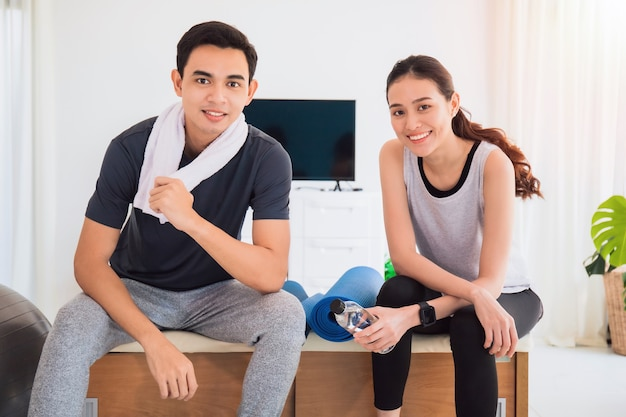 Asian young lover couple talking after play yoga and exercise at home background.