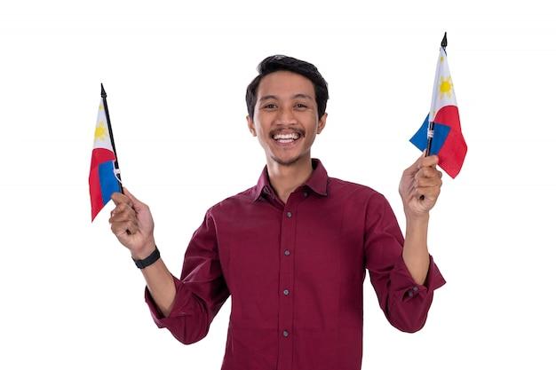 フィリピンの旗を保持しているアジアの若い男性